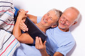 Senior Couple with Tablet in Bed — Stock Photo