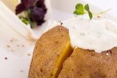 Baked jacket potato with sour cream sauce — Stock Photo