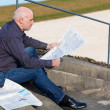 Man sitting on steps reading a newspaper — Stock Photo #54160633