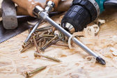 Drill with timber, screwdrivers and screws — Stock Photo