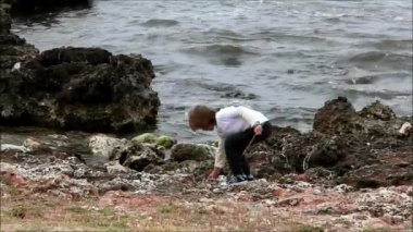 Boy throwing stones into the ocean — Stock Video