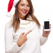 Woman in a Santa hat pointing on phone — Stock Photo #55946603