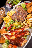 Mixed meats, salad and French fries — Stock Photo