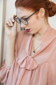 Red haired businesswoman  looking in window — Stock Photo