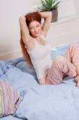 Young woman in pajamas resting on bed — Stock Photo