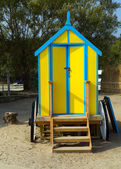 Seaside changing room bath car hut with wooden wheels in yellow and blue brightly coloured — Stock Photo