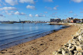 View towards Poole harbour and quay Dorset England UK with sea and sand on a beautiful day with blue sky and white clouds — Stock Photo