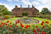 Strode House Barrington Court near Ilminster Somerset England uk with Lily pond garden and red dahlias — Stock Photo
