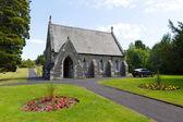 A Igreja do cemitério Bowness no Lago Windermere distrito Cumbria Inglaterra Reino Unido no verão com flores rosa e amarelas — Fotografia Stock