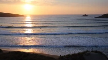 Sunset in Cornwall with surfers still surfing in the spring evening in Crantock bay and beach North Cornwall England UK near Newquay — Stock Video