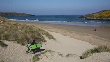 Surfers walking away from camera surfing beach Crantock bay North Cornwall England UK near Newquay — Stock Video
