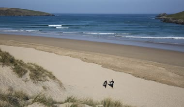 Surfers walking to camera Crantock bay and beach North Cornwall England UK near Newquay and on the South West Coast Path in spring with blue sky and sea — Stock Video