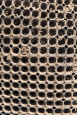 Honeycombe like pattern with many holes or circles on a texture or background with grains of sand — Stock Photo