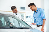Car Sales Consultant Showing a New Car to a Potential Buyer — Stock Photo