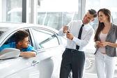 Car Salesman Invites Customers at Showroom. — Stock Photo