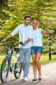 Happy Couple with bicycle in park. — Stock Photo