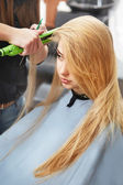 Hairdresser curling hair with straightener — Stock Photo