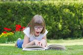 Menina lendo um livro em um jardim — Fotografia Stock