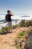 Man looking into binoculars in Madeira viewpoint — Stock Photo