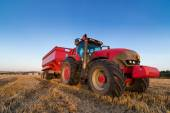 Agriculture tractor and trailer on a stubble field — Stock Photo