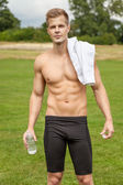 Muscular young man with a water bottle — Foto Stock