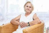 Portrait of an elderly lady sitting in a chair — Stock Photo