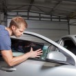 Applying tinting foil onto a car window — Stock Photo #74501199