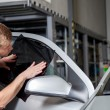 Applying tinting foil onto a car window — Stock Photo #74501267