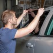 Applying tinting foil onto a car window in a workshop — Stock Photo #74501327