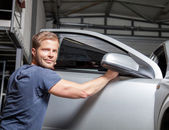 Applying tinting foil onto a car window — Stock Photo