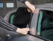 Applying tinting foil on a car window — Stock Photo