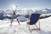 Cross ski and Empty sun-lounger at mountains — Stock Photo