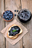 Bread with blueberry jam and jam in glass jar — Stock Photo