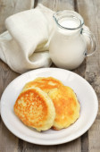 Fritters and milk jug on rustic table — Stock Photo