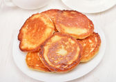 Fritters with honey on white plate — Stock Photo