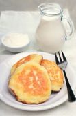 Fritters, milk jug and sour cream  — Stock Photo