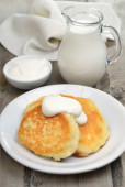 Fritters with sour cream and milk jug  — Stock Photo