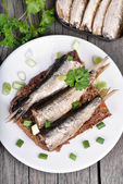 Sandwich with sprats on wooden table — Stock Photo