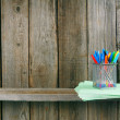Pens and writing-books on a wooden shelf. — Stock Photo #51917393