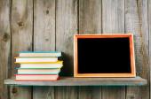 La tableta y libros en un estante de madera. — Foto de Stock