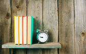 Alarm clock and books on wooden shelf. — Stock Photo