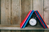 Alarm clock and writing-books on a wooden shelf. — Stock Photo
