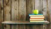 Multi-coloured books and green apple . — Stockfoto