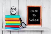 Back to school. Books and an alarm clock . — Stock Photo
