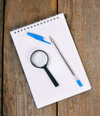 笔记本、 笔和木制的背景上的放大镜. — 图库照片