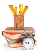 Books, an alarm clock and school tools. — Stock Photo