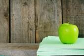 Apple and writing-books on a wooden shelf. — Φωτογραφία Αρχείου