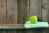 Apple and writing-books on a wooden shelf. — 图库照片