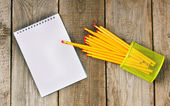 Notebook and pencils on wooden background. — Stock Photo