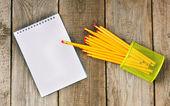 Notebook a tužky na dřevěné pozadí. — ストック写真